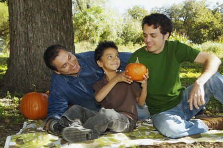 only three people: Multi-ethnic family with pumpkins under tree