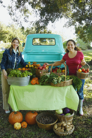 bestowing: Hispanic women at organic farm stand LANG_EVOIMAGES