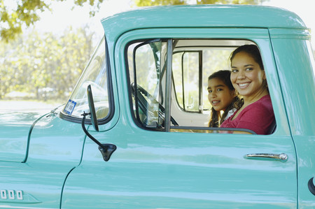 leaning on the truck: Hispanic mother and daughter driving truck