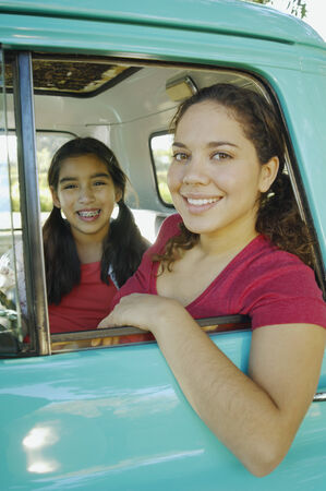 leaning on the truck: Hispanic mother and daughter sitting in truck