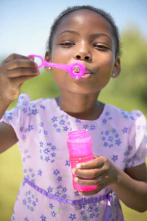 blowing bubbles: African girl blowing bubbles