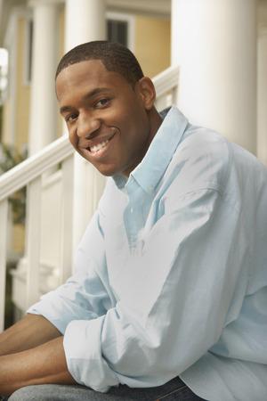 African man sitting on porch steps Banco de Imagens