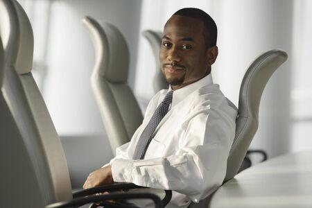 afroamericanas: Empresario afroamericano que se sienta en la silla LANG_EVOIMAGES