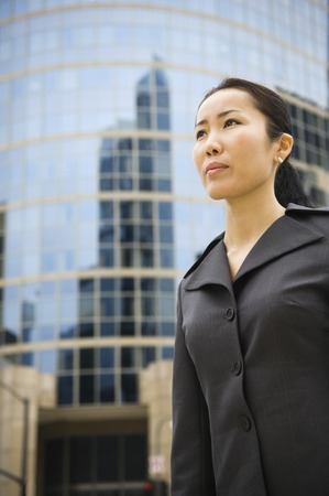 disgruntled: Asian businesswoman in front of high-rise
