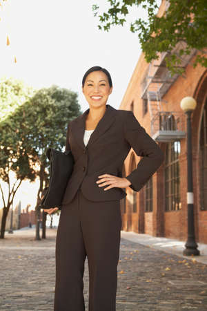 prevailing: Asian businesswoman with hand on hip LANG_EVOIMAGES
