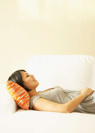 restful: Asian woman laying on sofa