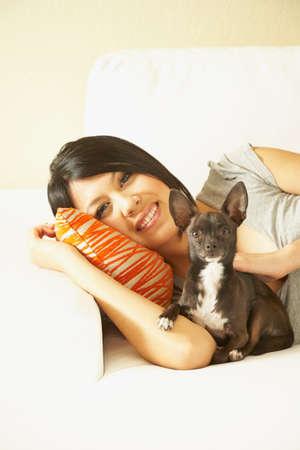 davenport: Asian woman and dog laying on sofa