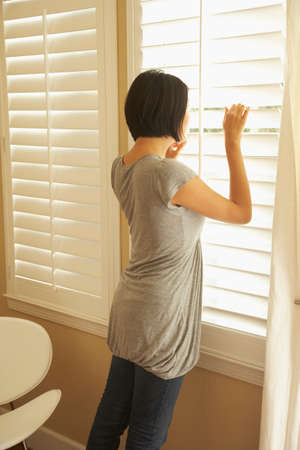 relishing: Asian woman looking out window