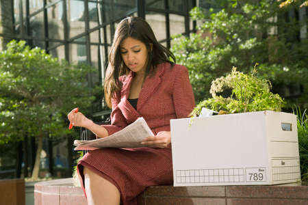 terminating: Indian businesswoman reading newspaper