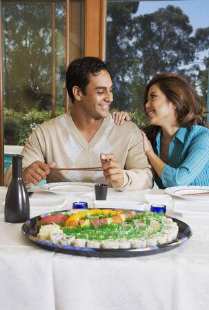 disrupting: Multi-ethnic couple eating sushi LANG_EVOIMAGES
