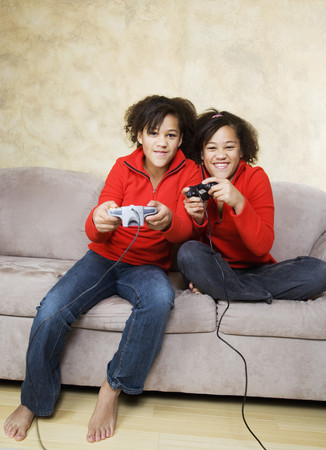 rubbing noses: African twin sisters playing video games