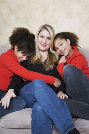 playing on divan: Multi-ethnic mother and twin daughters hugging LANG_EVOIMAGES