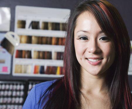 tinte de cabello: Mujer asi�tica en frente de muestras de tinte para el cabello