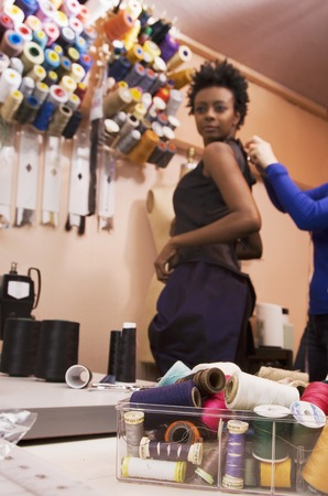 wearying: African woman trying on dress at seamstress shop