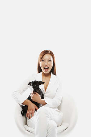 pampered pets: Asian businesswoman holding dog