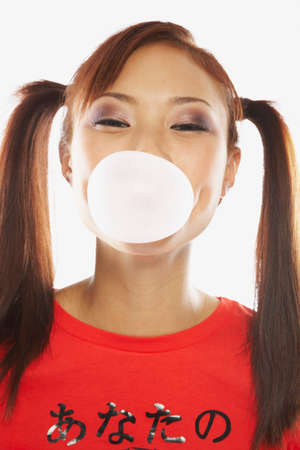casualness: Asian woman blowing bubble with bubble gum