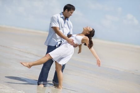jesting: Hispanic couple dancing at beach LANG_EVOIMAGES