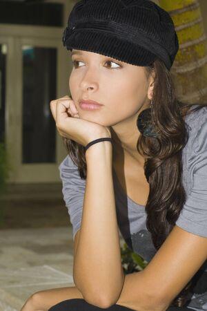 Hispanic woman resting chin on hand Stock Photo