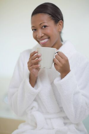 exactitude: African woman in bathrobe drinking coffee