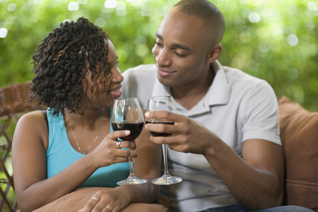 African couple toasting with wine Stock Photo