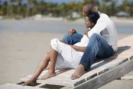 Multi-etnische paar knuffelen op het strand Stockfoto
