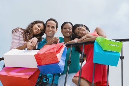 Hispanic friends holding shopping bags Stockfoto