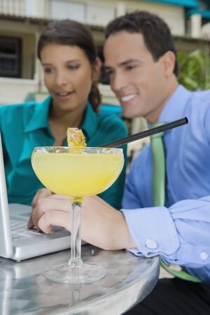 skepticism: Cocktail in front of Hispanic couple looking at laptop LANG_EVOIMAGES