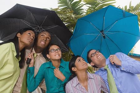 late twenties: Hispanic businesspeople standing under umbrellas
