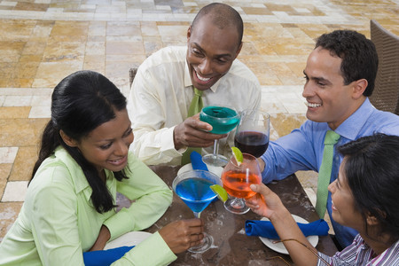Hispanic couples toasting with cocktails Фото со стока