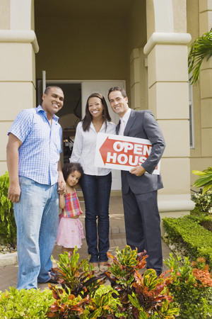 Hispanic real estate agent and African family in front of house 스톡 콘텐츠