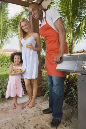 barbecuing: Mixed Race family barbecuing