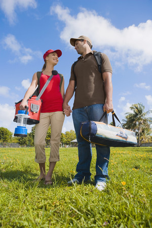 Hispanic couple carrying camping supplies Stock Photo