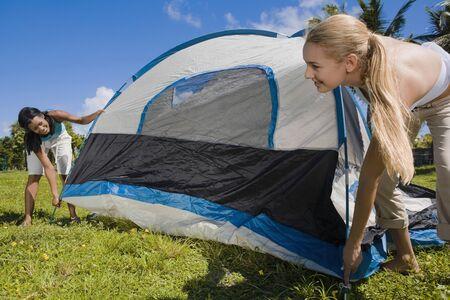 Hispanic women setting up tent