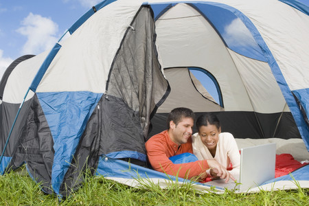 intriguing: Hispanic couple looking at laptop in tent LANG_EVOIMAGES