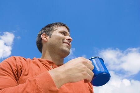 adventuresome: Hispanic man drinking coffee outdoors