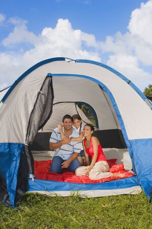 unconcerned: Hispanic family sitting in tent