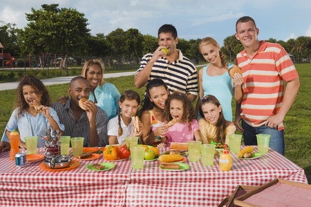 munching: Multi-ethnic friends eating at picnic table LANG_EVOIMAGES