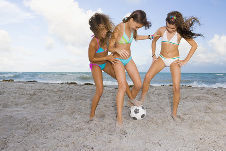 three girls: Multi-ethnic girls playing soccer at beach LANG_EVOIMAGES