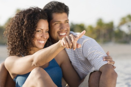 mischievious: Hispanic couple hugging and pointing