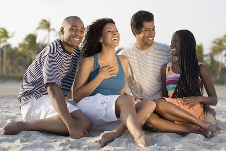 lighthearted: Multi-ethnic couples sitting on beach LANG_EVOIMAGES