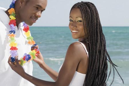 African woman touching lei around husband's neck