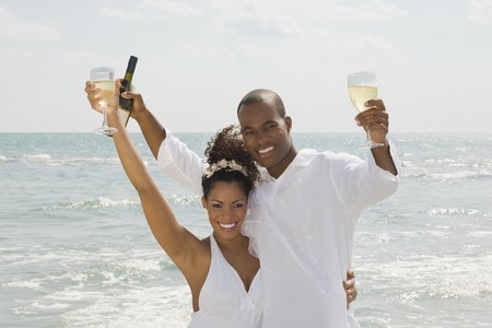 Multi-ethnic couple holding wine at beach 스톡 콘텐츠