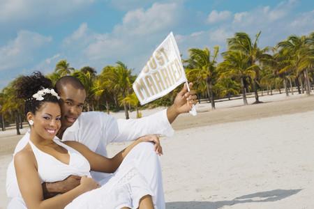 Multi-ethnic bride and groom at beach Imagens