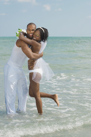 milepost: African bride and groom hugging at beach LANG_EVOIMAGES