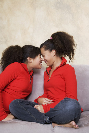 rubbing noses: African twin sisters rubbing noses