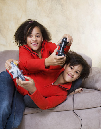 playing on divan: African twin sisters playing video games