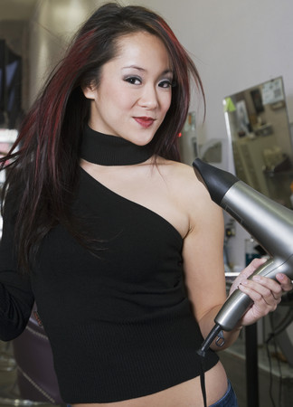 front raise: Asian hair stylist blow drying hair