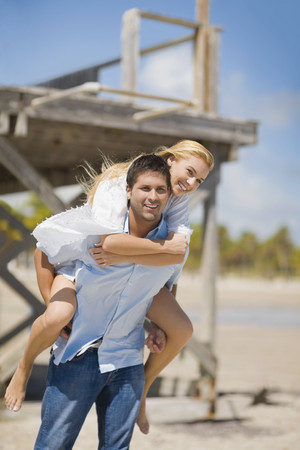 unconcerned: Hispanic man giving piggy back ride to girlfriend