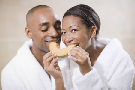 African couple in bathrobes eating melon