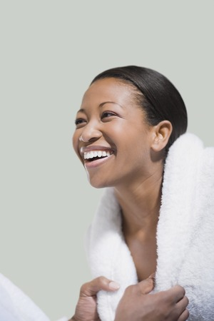African woman in bathrobe laughing